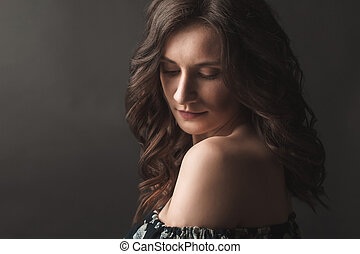 Beautiful brunette woman in the shadows
