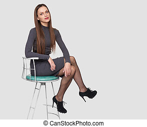 brunette woman is sitting on a chair isolated