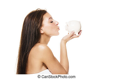 beautiful brunette woman kissing a piggy bank on white background