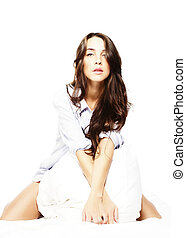 beautiful brunette woman kneeling in bed on white background