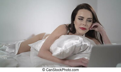 Beautiful brunette woman lying on white silk bed using laptop