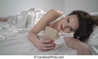 Beautiful brunette woman lying on white silk bed using smartphone