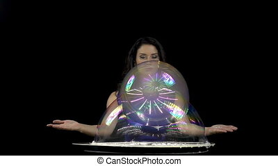 Beautiful brunette woman making large soap bubbles