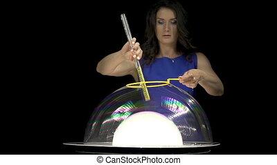 Beautiful brunette woman making soap bubbles