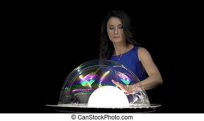 Beautiful brunette woman mixing soap bubbles