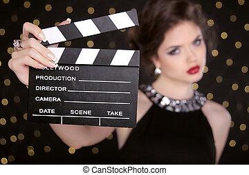 Beautiful brunette woman model holding film clap board...