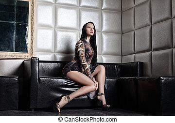 Beautiful brunette woman on sofa in nightclub