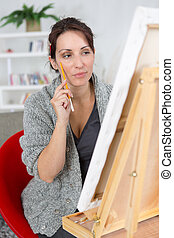 beautiful brunette woman painting on canva