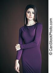 Beautiful brunette woman portrait posing on dark background