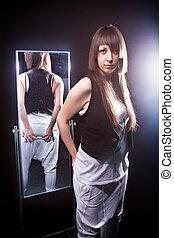 Beautiful brunette woman posing against mirror