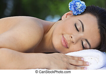 Beautiful Brunette Woman Relaxing At Health Spa Wth Blue Flower