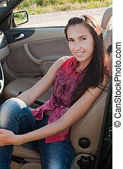 Beautiful brunette woman sitting in cabrio