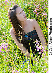 Beautiful brunette woman sitting in field