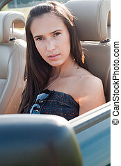 Beautiful brunette woman sitting in the car