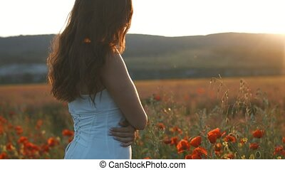 Beautiful brunette woman standing in poppies field