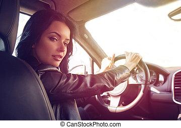 Beautiful brunette woman steers car expensive car