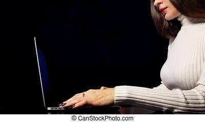 Beautiful brunette woman typing and using trackpad of her laptop. Isolated against black background.