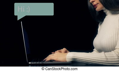 Beautiful brunette woman typing on her laptop against black background. Conceptual computer related motion graphics inscriptions