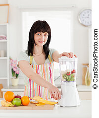 Beautiful brunette woman using a mixer while standing