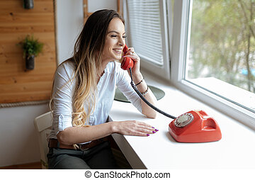 Beautiful brunette woman using old retro telephone at home