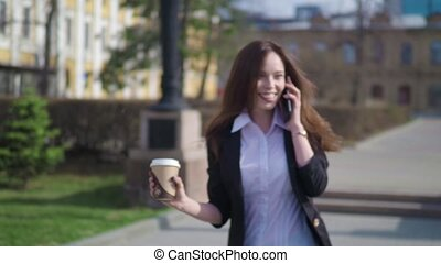 Beautiful brunette woman walking the city street and talking on the cell phone. Woman walking with coffee to go