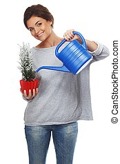 Beautiful brunette woman watering plant in red pot