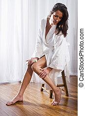 Beautiful brunette woman wearing bathrobe applying lotion to...