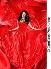 Beautiful brunette woman wearing in magnificent red dress on fabric texture background