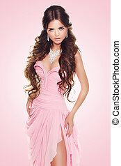 Beautiful brunette woman wearing in sexy luxury dress over pink background. Fashion beauty model girl posing.