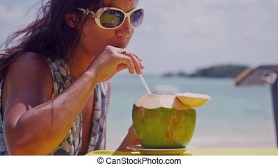Beautiful brunette woman wearing sunglasses drinking fresh...