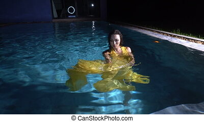 Beautiful brunette woman wearing yellow dress in the swimming pool