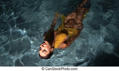Beautiful brunette woman wearing yellow dress in the swimming pool