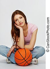 Beautiful brunette woman with a basketball