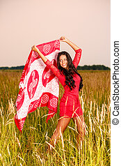beautiful brunette woman with a scarf in a field at sunset