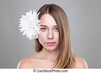 Beautiful brunette woman with a white flower