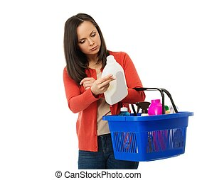 Beautiful brunette woman with basket reading label on...