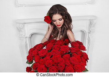 Beautiful brunette woman with bouquet of many red roses flowers at interior apartment, valentines day.