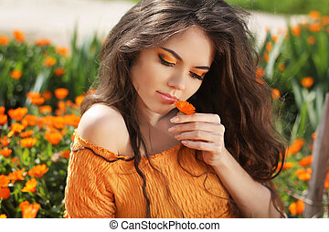 Beautiful brunette woman with colored makeup smelling flower, over marigold flowers field