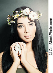 Beautiful brunette woman with cotton flowers in her hair and hand. Fashion photo