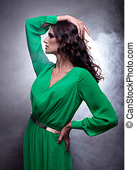 beautiful brunette woman with curly long hair in green dress