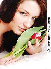 Beautiful brunette woman with flower on white bed