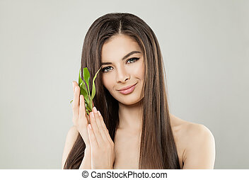 Beautiful Brunette Woman with Green Bamboo Leaves on Banner Background