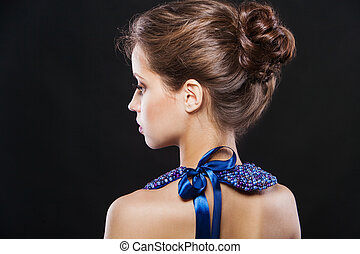 Beautiful brunette woman with luxury necklace and bow on her back