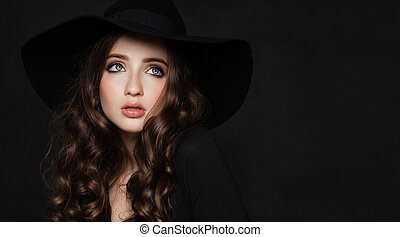 Beautiful Brunette Woman with Perfect Curly Hairstyle and Makeup. Perfect Model wearing Black Hat