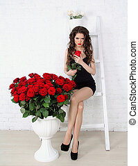 Beautiful brunette woman with red roses bouquet, leaning on old brick wall. Valentines day.