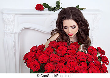 Beautiful brunette woman with red roses bouquet of flowers at interior apartment, Valentines day.