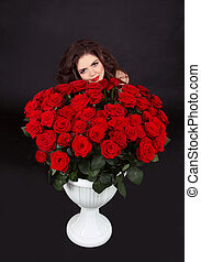 Beautiful brunette woman with red roses bouquet, valentines day. Isolated on black background.