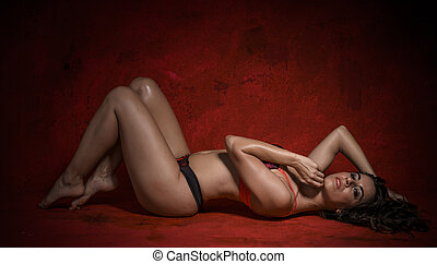 Beautiful brunette woman with sensual lingerie on textured background in red. sexy and provocative poses