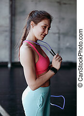 beautiful brunette woman with skipping rope in the gym