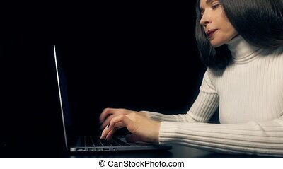Beautiful brunette woman working on her laptop against black background. 4K video